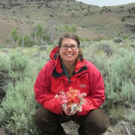 Hillary holding a boquet of indian paintbrush flowers and sage.